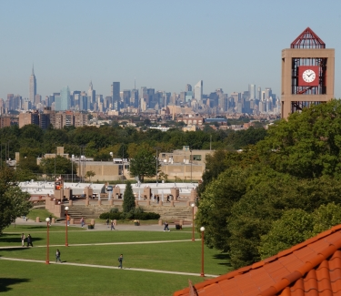 Photograph of the Queens College library clock tower with the Manhattan skyline in the distance.